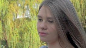 Ståenden av en härlig blond flicka med vinkande hår som ser kameran i, parkerar på solig dag lager videofilmer
