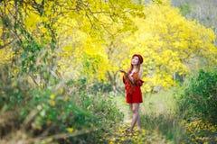 Ståenden av en härlig flicka bland guling blommar i naturen Arkivfoton