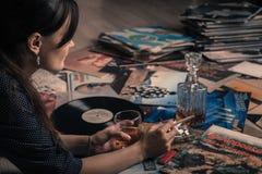 Ståenden av en härlig flicka, glass whisky som lyssnar till musik från vinylLP, antecknar tappning Arkivbild