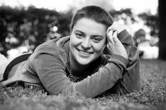 Ståenden av en härlig flicka med kort hår och gröna ögon ligger på gräset som ler och ser kameran arkivfoton