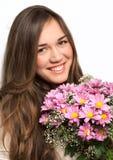 Ståenden av en härlig flicka med långt hår och en rosa färg blommar arkivbild