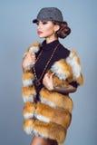 Ståenden av en härlig glam tatuerade modellen med det provokativa sminket som bär den svarta klänningen, stilfullt rävomslag och  royaltyfria foton