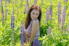 Ståenden av en härlig kvinna med gröna ögon bryner långt hår på ett fält av blommor Flickan i den purpurfärgade klänningen ler oc royaltyfri fotografi