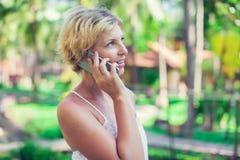 Ståenden av en härlig le kvinna som använder en mobiltelefon, överträffar royaltyfria foton