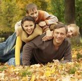 Den lyckliga familjen som ligger i höst, parkerar Royaltyfri Fotografi
