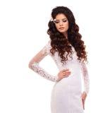 Ståenden av en härlig ung brunettflicka i vit snör åt bröllopsklänningen royaltyfri foto
