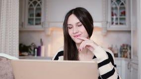 Ståenden av en härlig ung brunettkvinna använder bärbara datorn i ljust äta middag arkivbilder