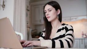 Ståenden av en härlig ung brunettkvinna använder bärbara datorn i ljust äta middag arkivfoton