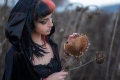 Ståenden av en härlig ung individ, den excentriska kvinnan tycker om solrosblomningar och frö på fältet royaltyfria foton