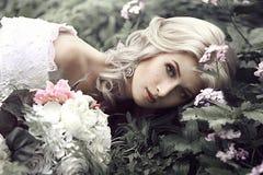 Ståenden av en härlig ung kvinna som en prinsessa ligger i en skog med blommor Arkivfoton