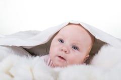 Ståenden av en krypning behandla som ett barn på sängen Arkivfoto