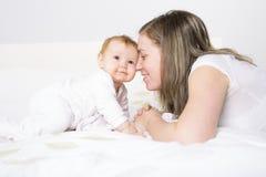 Ståenden av en krypning behandla som ett barn på sängen i hennes rum Arkivfoton