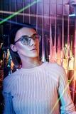 Ståenden av en kvinna i neon färgade reflexionsexponeringsglas i bakgrunden Bra vision, perfekt makeup på flickaframsida Härlig W arkivbild