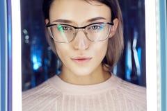 Ståenden av en kvinna i neon färgade reflexionsexponeringsglas i bakgrunden Bra vision, perfekt makeup på flickaframsida Härlig W royaltyfria bilder
