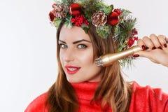 Ståenden av en kvinna med en grankrans med kottar på hennes huvud, rymmer i hennes hand en dysa för ett kosmetiskt tillvägagångss fotografering för bildbyråer