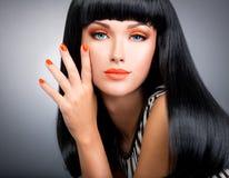 Ståenden av en kvinna med rött spikar och glamourmakeup Arkivbild