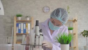 Ståenden av en kvinnalaborant för en studie av växten genom att använda ett mikroskop lager videofilmer