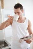 Ståenden av en le dricka tea för man fördriver läsning nyheterna Royaltyfri Bild