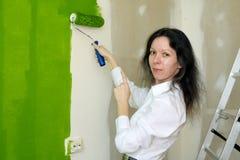 Ståenden av en le nätt ung kvinna målar den gröna innerväggen med rullen i ett nytt hem och pekar på hennes arbete royaltyfri fotografi