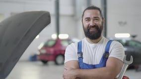 Ståenden av en le skäggig mekaniker som poserar med ett skiftnyckelanseende på en automatisk reparation, shoppar på bakgrunden av arkivfilmer