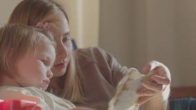 Ståenden av en le ung gullig moder och dottern som läser en bok som ligger och, kopplar av i sängen lager videofilmer