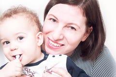 Ståenden av en lycklig moder poserar framme av kamera med hennes bab Arkivbild