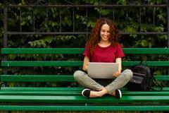 Ståenden av en lycklig ung kvinna som ler genom att använda bärbara datorn som sitter på bänk parkerar in Inneh?ll lutning- och u arkivbild