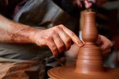 Ståenden av en manlig keramiker i förklädeformer bowlar från lera, den selektiva fokusen, närbild royaltyfri foto