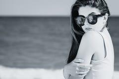St?enden av en n?tt flicka med l?ngt h?r i moderiktig solglas?gon med g?mma i handflatan reflexionen som poserar p? stranden fotografering för bildbyråer