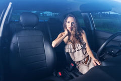 Ståenden av en nätt flicka som kör en bil, sköt till och med vindrutan utomhus Arkivfoton