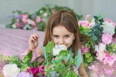 Ståenden av en nätt liten flicka i en turkosklänning sniffar blommor i en studio arkivfoto