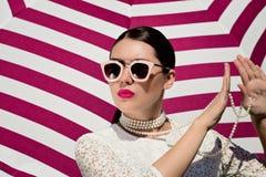 Ståenden av en nätt ung kvinna i vit snör åt klänningen, den vita pärlemorfärg halsbandet och solglasögon med ljusa målade kanter arkivbild