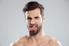 Ståenden av en rubbning irriterade den nakna skäggiga manvisningtungan Fotografering för Bildbyråer