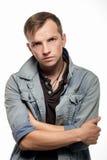 Ståenden av en säker ung man i jeans klår upp på en vit arkivbild
