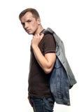 Ståenden av en säker ung man med jeans klår upp på en vit b royaltyfria foton