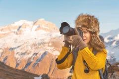 Ståenden av en söt turist- flicka i en stor pälshatt tar bilder på hennes digitala kamera i bergen Royaltyfri Fotografi