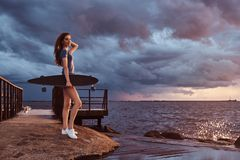 Ståenden av en sinnlig flicka rymmer en skateboard, medan att stå på stranden är att tycka om fantastiskt mörkt molnigt väder und fotografering för bildbyråer