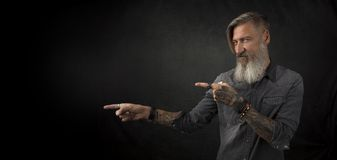 Ståenden av en skäggig hipster, som pekar med hans fingrar till något, isolerade på en svart bakgrund arkivfoton