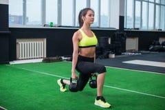 Ståenden av en sportig kvinna som gör utfall med hantlar som utarbetar ben, tränga sig in Royaltyfri Foto