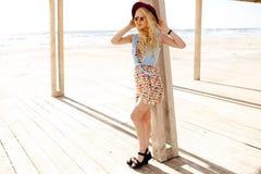 Ståenden av en stilfull blond flicka med rund solglasögon, våghår och den burgundy hatten, tycker om solljuset på havet royaltyfri bild