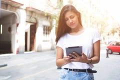 Ståenden av en stilfull hipsterflicka använder den digitala minnestavlan för navigering i stads- inställning arkivfoton