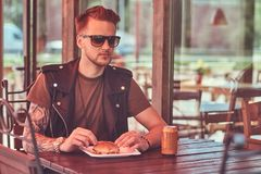 Ståenden av en stilig stilfull hipstergrabb sitter på en tabell som beställas en hamburgare, och sodavatten, äter middag på vägre royaltyfri bild
