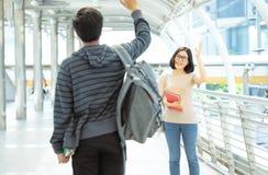 Ståenden av en ung asiatisk kvinna av universitetsstudenter säger hälsningar som hälsar hennes pojkvän på gatan fotografering för bildbyråer