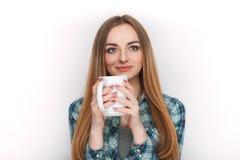 Ståenden av en ung förtjusande blond kvinna i blå plädskjorta som tycker om hennes varma hemtrevliga drink i stor tom vit, rånar Arkivbilder