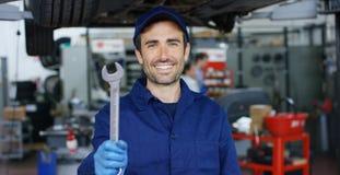 Ståenden av en ung härlig bilmekaniker i en bilreparation shoppar, händer med en skruvnyckel Begrepp: reparation av maskiner, fel Royaltyfri Bild