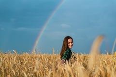 Ståenden av en ung kvinna i ett fält med vete gå i ax på en regnbågebakgrund royaltyfria foton