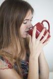 Den unga kvinnan med härlig gräsplan synar med rött kaffe kuper Royaltyfri Foto