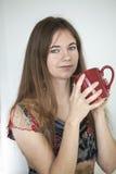 Den unga kvinnan med härlig gräsplan synar med rött kaffe kuper Royaltyfri Fotografi