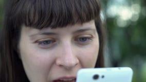 Ståenden av en ung kvinna som använder en smartphone, tar hon en selfie arkivfilmer