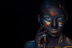 Ståenden av en ung kvinna, som poserar, täckte med svart målarfärg arkivfoton